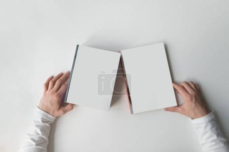 Photo pour Les mains tiennent des livres blancs sur un fond clair. Livres blancs avec les mains sur une table blanche. Pose plate - image libre de droit