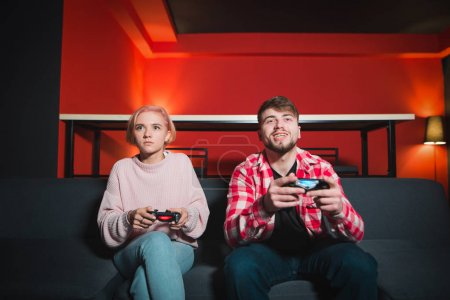 A couple plays the game on the console. A man smiling girl is sad. A man wins a woman in a video game