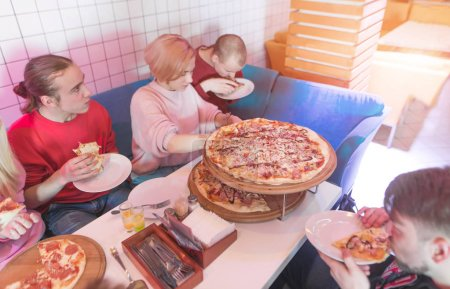 Students eat a great appetizer pizza in a cozy restaurant. A group of young people eating pizza in a pizzeria. Lunch with friends and pizza