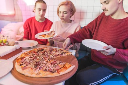 A group of friends sits in a pizzeria and eats a big pizza. Young people eat pizza at the restaurant on weekends.