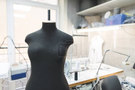 Black sewing mannequin on a background of workplace seamstresses. Sewing concept.