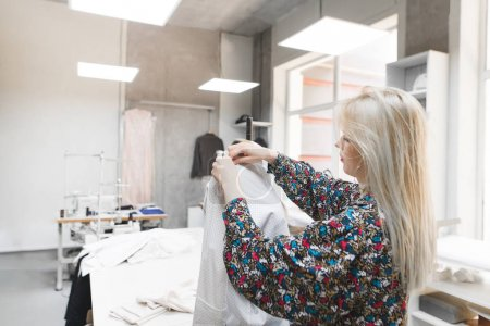 The seamstress stands in the studio near the mannequin and adjusts the clothes. Creation of fashion clothes. Seamstress and dummy with clothes. Sewing concept