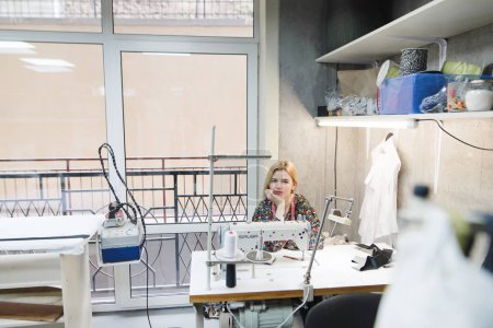 A young seamstress sits at the workplace in a modern studio. Modern designer clothing design studio