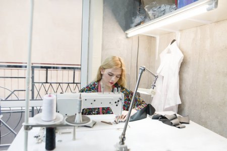 Portrait of a young seamstress at work on a professional sewing machine. Attractive seamstress at work in the studio. Create stylish clothes in a contemporary design studio