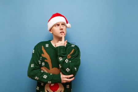Photo for Portrait of pensive young man wearing santa hat and green christmas sweater, looks away at blank space and thinks isolated on blue background. Copy space - Royalty Free Image