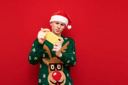 Photo pour Jeune homme drôle en tenue de Noël jouant à des jeux mobiles sur un smartphone, regardant un écran au visage tendu, portant un chandail chaud et un chapeau santa. Joueur de Noël jouant sur un smartphone - image libre de droit