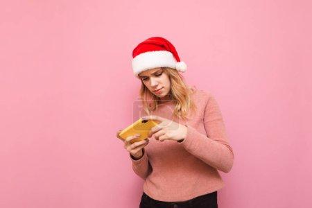 Photo pour Concentré gamer girl dans le chapeau de Noël jouer à des jeux mobiles sur smartphone sur fond rose. Portrait de jeune fille concentrée dans santa chapeau jouer à des jeux sur le téléphone. Jeux de Noël. X-mas - image libre de droit