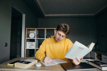 Photo pour Beau jeune étudiant masculin dans des études de vêtements décontractés jaunes à la maison à une table sur le fond d'une chambre confortable, tient le livre à la main et écrit intensément dans un carnet avec un stylo dans les dents . - image libre de droit