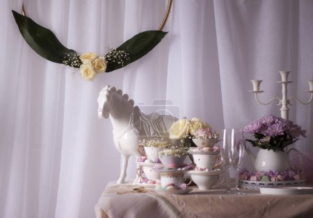 Photo for Closeup of horse statue on table with cups, sweets and flowers - Royalty Free Image