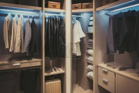 Photo for Black and white cloths hanging in wooden wardrobe at home - Royalty Free Image
