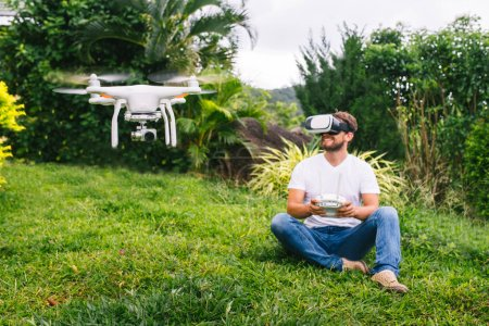 Photo for A man in a virtual reality helmet sitting next to the drone. A man sits on the grass - Royalty Free Image