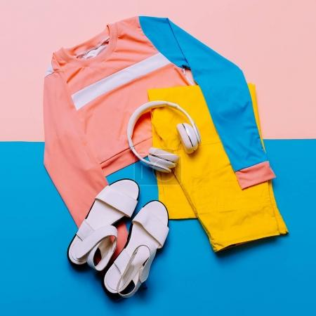Stylish sports blouse and pants. Pastel trend. Sandals, earphone