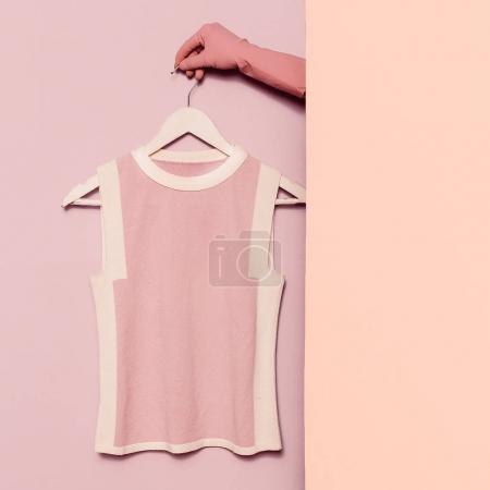 Stylish clothes. Minimal fashion. Pink top on a hanger. Wardrobe