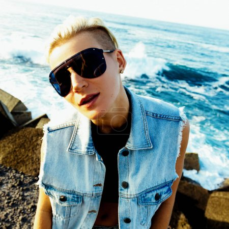 Stylish blonde in a denim waistcoat and trendy sunglasses. ocean