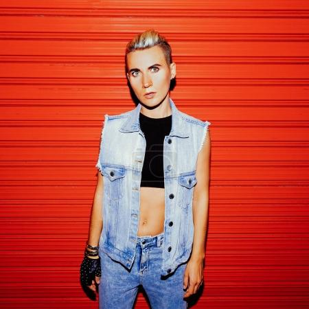 Photo pour Fille élégante en tenue de jeans sur un fond rouge. Style de rue - image libre de droit