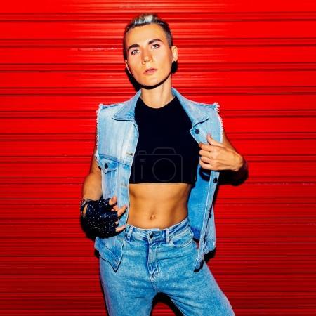 Photo pour Élégant modèle Tom garçon en tenue de jeans sur fond rouge. Style de rue - image libre de droit