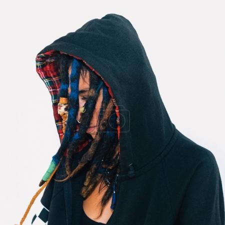 Model in a sweatshirt with dreadlocks and piercings. Fashion acc