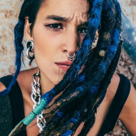 Portrait of a spanish girl with trendy dreadlocks and piercings.