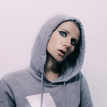 Girl Tomboy in a sweatshirt and a hood. Street fashion vibes