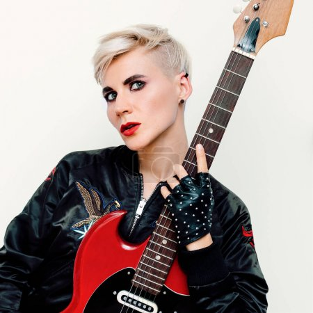 Blond Model with electro guitar. Rock style fashion