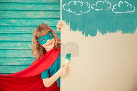 Superhero child painting the wall