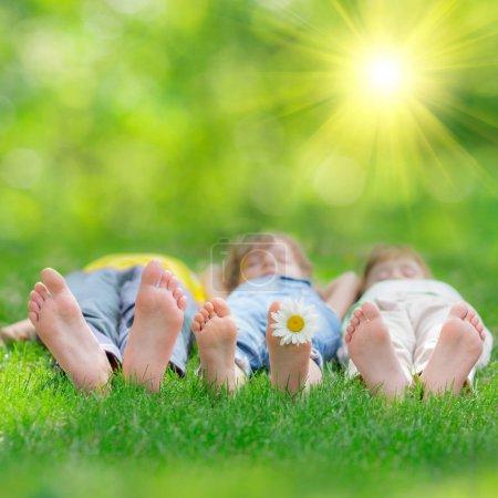 Photo pour Enfants heureux jouant à l'extérieur. Les enfants s'amusent au parc printanier. Amis couchés sur l'herbe verte - image libre de droit