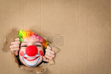 Photo for Funny kid clown looking through hole on cardboard. Child playing at home. 1 April Fool's day concept. Copy space. - Royalty Free Image