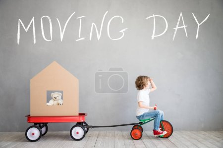 Photo for Happy child playing into new home. Kid having fun indoor. Moving house day and express delivery concept - Royalty Free Image