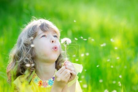 Happy child blowing dandelion flower