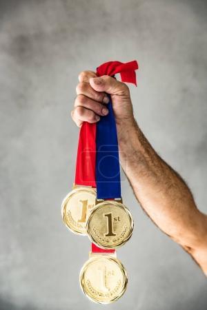 Photo pour Senior homme tenant à la main les médailles. Concept de victoire et succès - image libre de droit