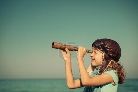 Photo for Child pretend to be sailor. Happy kid playing outdoor against sea and sky background. Summer vacation and travel concept - Royalty Free Image
