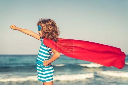 Superhero child on beach