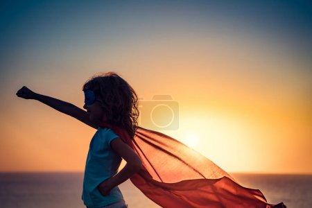 Foto de Niño superhéroe en la playa. Super héroe chico divertirse al aire libre. Concepto vacaciones de verano - Imagen libre de derechos