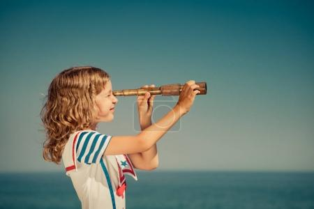 Child with vintage spyglass on summer vacation