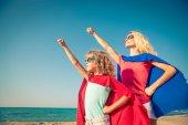 Family of superheroes on the beach.