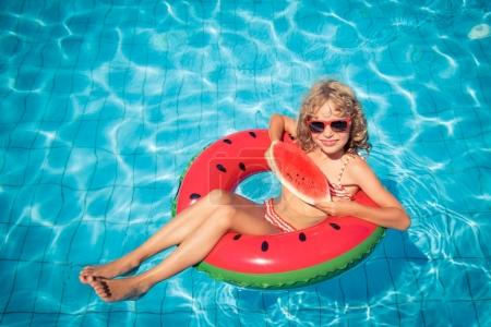 Child with watermelon in swimming pool