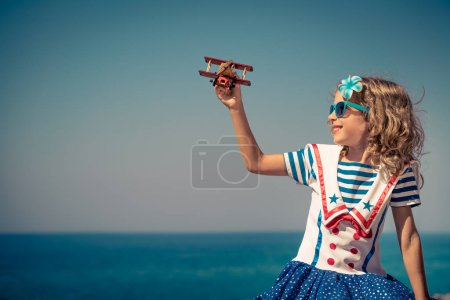 Child with wooden airplane on summer vacation