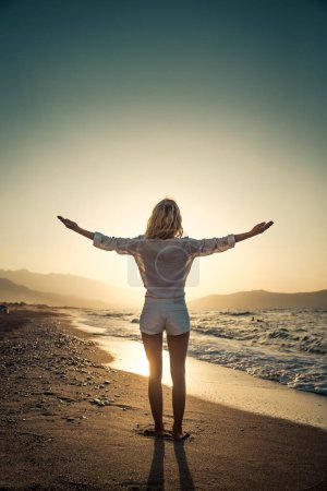 Photo pour Femme heureuse avec les mains ouvertes sur fond bleu mer et ciel. Personne qui s'amuse pendant les vacances d'été. Concept de liberté et d'imagination - image libre de droit