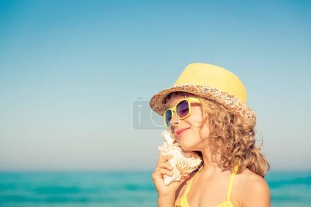 Photo for Happy child listen seashell on the beach. Portrait of girl against blue sea and sky background. Kid having fun on summer vacation. Dream and imagination concept - Royalty Free Image