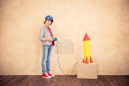 Photo for Kid with jet pack. Child playing at home. Success, imagination and innovation technology concept - Royalty Free Image