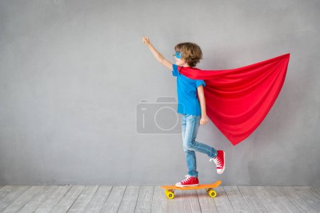 Child with cloak and skateboard