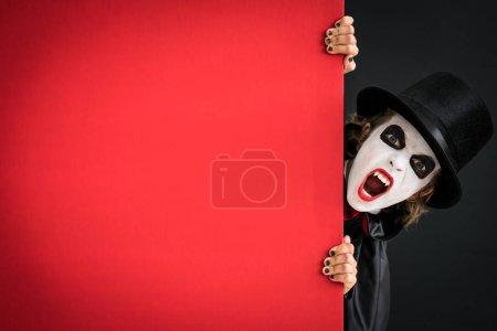 Photo pour Enfant drôle habillé costume d'Halloween. Le gamin a peint un vampire terrible tenant la bannière vide. Concept de vacances d'automne - image libre de droit