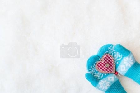 hands in mittens holding decorated heart