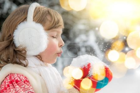 girl blowing at handful of snow