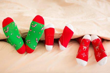 three pairs of feet in warm socks
