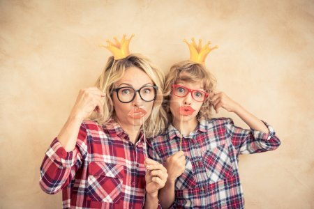 Photo for Funny woman and kid with fake mustache. Happy family playing in home - Royalty Free Image