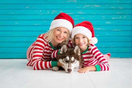 Photo for Happy mother, child and dog on Christmas eve. Kid and pet dressed in Santa Claus hat. Family having fun with husky at home. Chinese calendar new year concept - Royalty Free Image