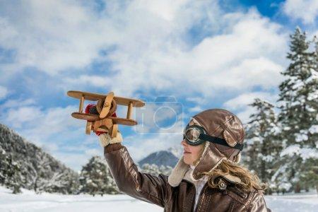 Photo pour Joyeux enfant jouant avec un avion jouet sur fond de ciel d'hiver. Le pilote s'amuse en plein air. Concept d'imagination et de liberté - image libre de droit