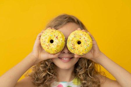 Photo pour Joyeux enfant tenant un beigne glacé. Portrait d'une fillette amusante sur fond jaune - image libre de droit