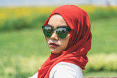 Portrait of happy young muslim woman red hijab over blurred the green field with yellow cosmos flowers under blue sky background.